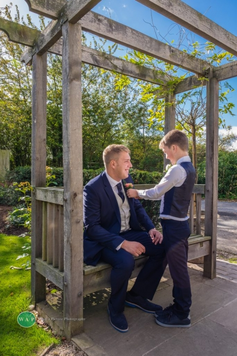 Fixing the grooms buttonhole by What a Picture Photography at Redhouse Barn