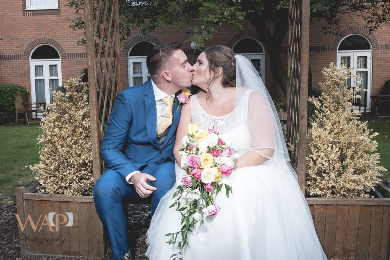 Kissing in the garden of the Regency Hotel during the wedding photography - 2019 special